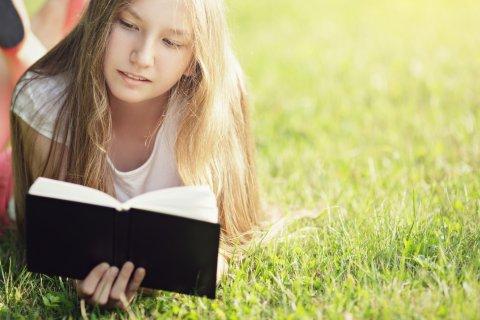 ילדה על דשא קוראת ספר