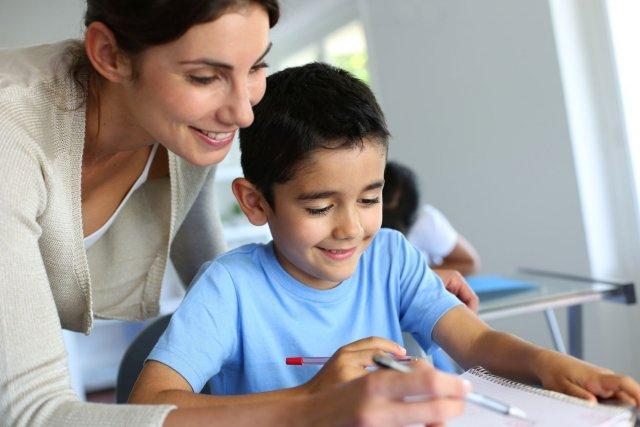 מורה מסייעת לילד בלימודים