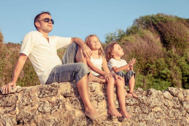 הורה וילדיו יושבים בחיק בטבע