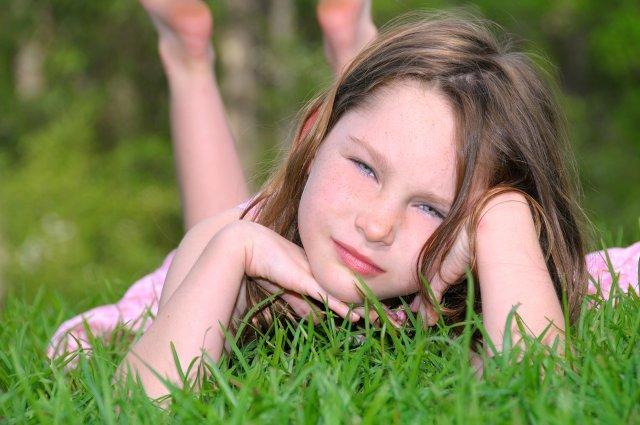 ילדה נשענת על הדשא